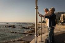 Senior couple standing at promenade near sea on a sunny day — Stock Photo