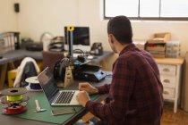 Rückansicht des Mechanikers mit Laptop auf Tisch in der Werkstatt — Stockfoto