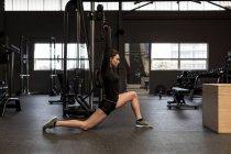 Fit mulher fazendo exercício de alongamento no estúdio de fitness — Fotografia de Stock