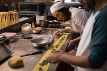 Уважний пекарів підготовка макарони у хлібобулочні — стокове фото