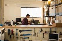 Механік, використовуючи мобільний телефон на стіл в майстерні — стокове фото