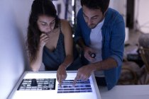Male photographer and female model discussing over negative filmstrip in photo studio — Stock Photo