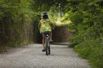 Vue arrière de la jeune fille à vélo sur la rue — Photo de stock
