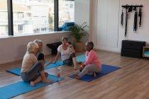Группа женщин старшего возраста, взаимодействующих друг с другом в центре йоги — стоковое фото