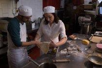 Boulangers à l'aide de machine pour la préparation de pâtes dans la boulangerie — Photo de stock