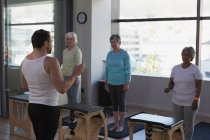 Trainer instructing group of senior women in yoga center — Stock Photo