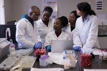 Groupe de techniciens de laboratoire discutant sur ordinateur portable dans la banque de sang — Photo de stock