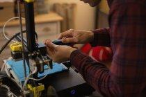 Mid section of mechanic adjusting die machine in workshop — Stock Photo