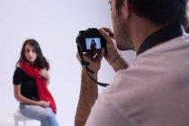 Мужской фотограф щелкает фотографиями модели в фотостудии — стоковое фото