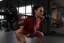 Bella donna che fa uno squat bilanciere nello studio fitness — Foto stock