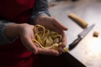 Tagliatelle en mano mientras baker hacer tagliatelle en panadería - foto de stock