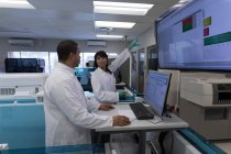Laboratory technicians discussing over display screen in blood bank — Stock Photo
