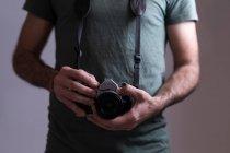 Середина мужского фотографа, стоящего с цифровой камерой — стоковое фото