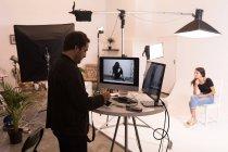 Мужчина-фотограф держит камеру в фотостудии — стоковое фото