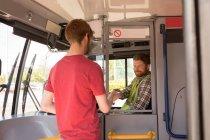 Учень приміського, приймаючи квиток від водія в сучасних зупинок — стокове фото