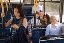 Weibliche Pendler mit Handy während der Fahrt im modernen bus — Stockfoto