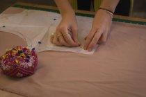 Créateur de mode épingler sur tissu dans le studio de mode — Photo de stock