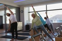 Trainer instructing group of senior women in performing yoga at yoga center — Stock Photo