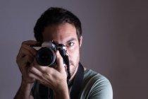 Мужчина фотограф, нажав фотографии с камеры в фото студии — стоковое фото