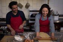 Жіночий Бейкер прокатки тісто для виготовлення макаронних виробів у хлібобулочні — стокове фото