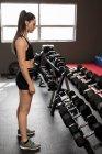 Forme femme regardant haltères sur la grille dans le studio de remise en forme — Photo de stock
