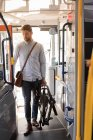 Smart man with folding bicycle entering in modern bus — Stock Photo