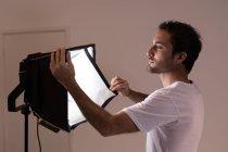 Männlicher Fotograf justiert Blitzlichter im Fotostudio — Stockfoto