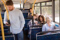 Smart male commuter using mobile phone while travelling in modern bus — Stock Photo