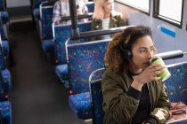 Young female commuter having coffee while travelling in modern bus — Stock Photo