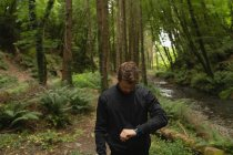 Young man looking at smart watch in forest — Stock Photo