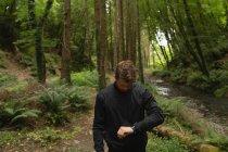 Молодой человек смотрит на умные часы в лесу — стоковое фото