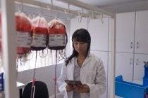 Technicien de laboratoire utilisant la tablette numérique dans la banque de sang — Photo de stock