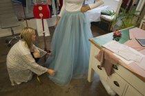 Fashion designer dressing customer in fashion studio — Stock Photo
