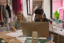 Diseñadores de moda trabajando en escritorio en el estudio de moda - foto de stock