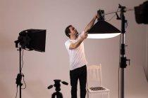 Male photographer adjusting strobe lights in photo studio — Stock Photo