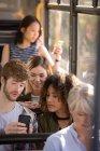 Друзів за допомогою мобільного телефону під час вашого перебування в сучасних зупинок — стокове фото