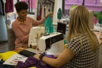 Fashion designers using sewing machine in fashion studio — Stock Photo