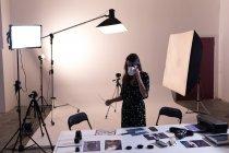Fotógrafa feminina tomando café enquanto olha para fotografias no estúdio de fotografia — Fotografia de Stock