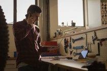 Молодой механик разговаривает по мобильному телефону в мастерской — стоковое фото