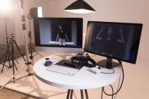 Женщина-модель позирует на экране компьютера в фотостудии — стоковое фото