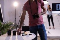 Мужчина-фотограф меняет объектив камеры в фотостудии — стоковое фото