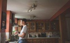 Homme a café dans la cuisine à la maison, vue latérale — Photo de stock