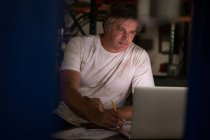 Male mechanic drawing a car model while using laptop in garage — Stock Photo