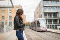 Vista lateral de la mujer con teléfono móvil en la plataforma en la estación - foto de stock