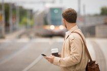Hombre usando el móvil mientras mira el tren en la plataforma - foto de stock