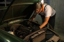 Male mechanic servicing a car in garage — Stock Photo