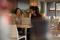 Jeune couple parlant entre eux dans un café — Photo de stock