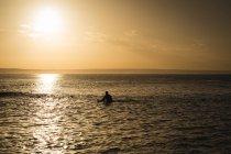 Surfer avec planche de surf surf sur mer pendant le coucher du soleil — Photo de stock