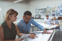 Executives discussing over blueprint on drafting table in office — Stock Photo