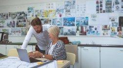 Ejecutivos discutiendo sobre tableta en el escritorio en la oficina - foto de stock